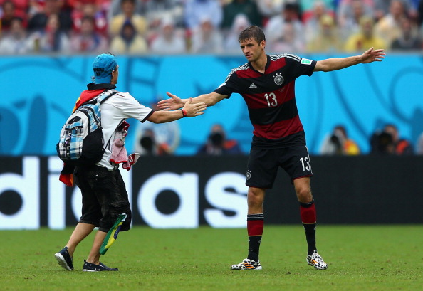 A pitch invader interacts with Thomas Mueller of Germany during the 2014 FIFA World Cup Brazil group G match between the United States and Germany at Arena Pernambuco on June 26, 2014.  (credit: Michael Steele/Getty Images)