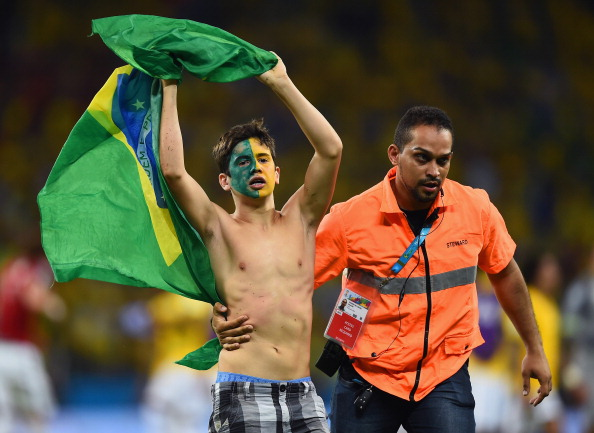 A pitch invader is escorted off the field by security during the 2014 FIFA World Cup Brazil Quarter Final match between Brazil and Colombia at Castelao on July 4, 2014 in Fortaleza, Brazil.  (credit: Laurence Griffiths/Getty Images)
