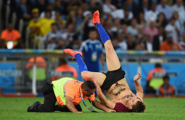 Security personnel tackle a pitch invader during the 2014 FIFA World Cup Brazil Final match between Germany and Argentina at Maracana on July 13, 2014 in Rio de Janeiro, Brazil.  (credit: Matthias Hangst/Getty Images)
