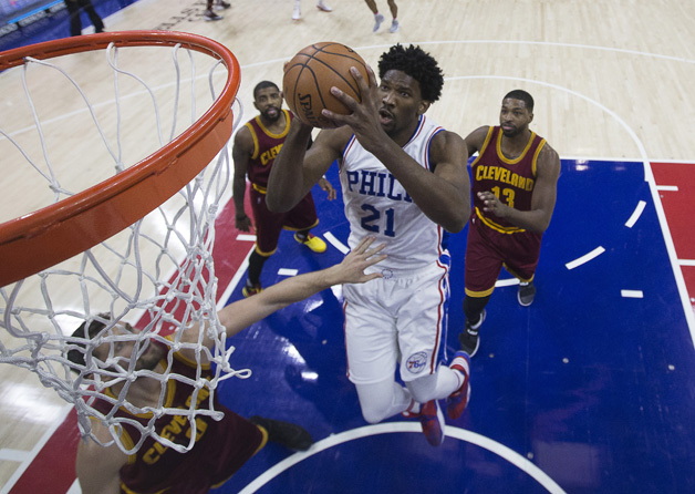 Joel Embiid #21 of the Philadelphia 76ers goes up for a shot against Kevin Love #0 and Tristan Thompson #13 of the Cleveland Cavaliers in the first quarter at Wells Fargo Center on November 27, 2016 in Philadelphia, Pennsylvania. The Cavaliers defeated the 76ers 112-108.
