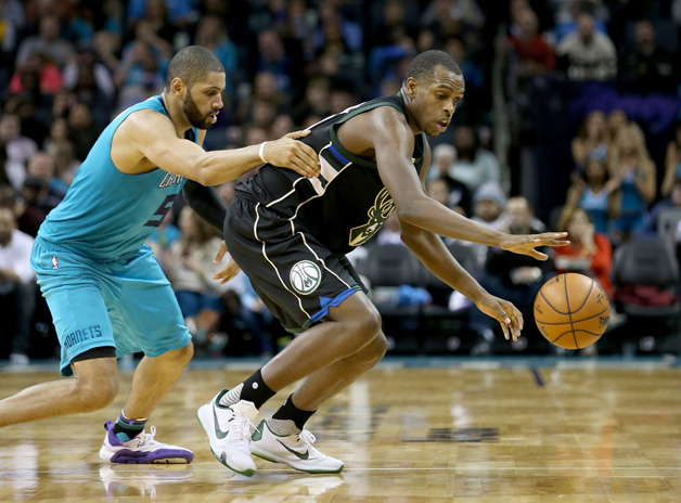 Khris Middleton #22 of the Milwaukee Bucks goes after a looes ball against Nicolas Batum #5 of the Charlotte Hornets during their game at Time Warner Cable Arena on January 16, 2016 in Charlotte, North Carolina.
