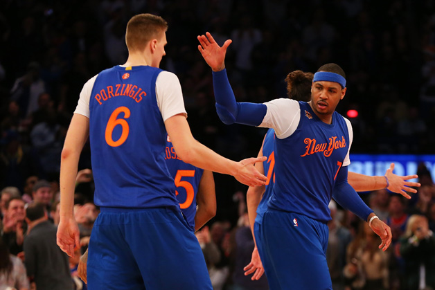 Carmelo Anthony #7 of the New York Knicks celebrates with Kristaps Porzingis #6 after hitting a basket against the Boston Celtics at Madison Square Garden on December 25, 2016 in New York City.