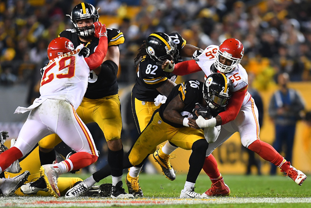 Le'Veon Bell #26 of the Pittsburgh Steelers is tackled by Dee Ford #55 of the Kansas City Chiefs in the first half during the game at Heinz Field on October 2, 2016 in Pittsburgh, Pennsylvania.