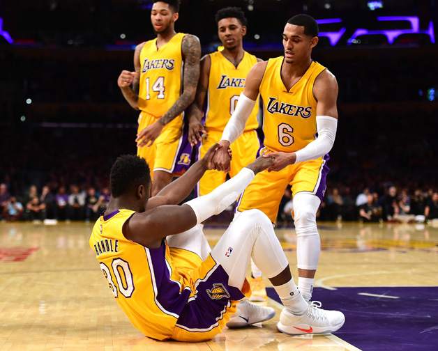 Julius Randle #30 of the Los Angeles Lakers gets helped up by Jordan Clarkson #6 as Nick Young #0 and Brandon Ingram #14 look on during a 101-89 Dallas Mavericks win at Staples Center on December 29, 2016 in Los Angeles, California.