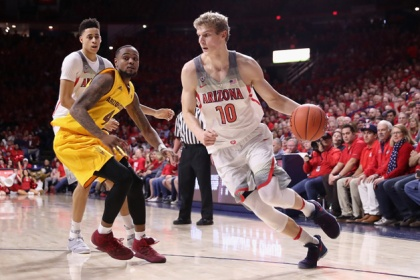 Lauri Markkanen #10 of the Arizona Wildcats drives the ball past Torian Graham #4 of the Arizona State Sun Devils during the first half of the college basketball game at McKale Center on January 12, 2017 in Tucson, Arizona.