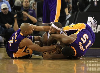 Derek Fisher #2 and Ron Artest #15 of the Los Angeles Lakers wrestle for the ball with DeMarcus Cousins #15 of the Sacramento Kings at ARCO Arena on November 3, 2010 in Sacramento, California.