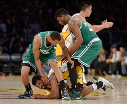Ronnie Price #9 of the Los Angeles Lakers hangs on to the ball with Avery Bradley #0 and Marcus Smart #36 of the Boston Celtics over him as Jeremy Lin #17 calls a timeout during a 118-111 Laker win at Staples Center on February 22, 2015 in Los Angeles, California.
