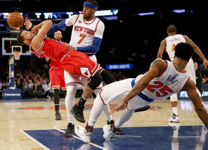 Michael Carter-Williams #7 of the Chicago Bulls is called for an offensive foul as he hits Derrick Rose #25 of the New York Knicks as Carmelo Anthony #7 of the Knicks looks on at Madison Square Garden on January 12, 2017 in New York City.