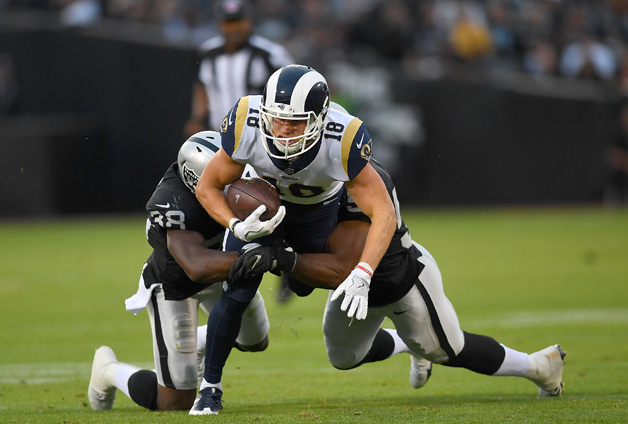 Cooper Kupp #18 of the Los Angeles Rams gets tackled by Cory James #57 and T.J. Carrie #38 of the Oakland Raiders during the first quarter of their preseason NFL football game at Oakland-Alameda County Coliseum on August 19, 2017 in Oakland, California.