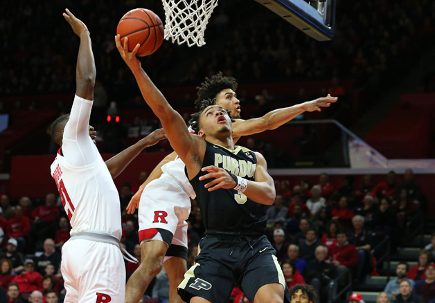 Carsen Edwards #3 of the Purdue Boilermakers attempts a layup as Mamadou Doucoure #21 and Geo Baker #0 of the Rutgers Scarlet Knights defends during the first half of a game at Rutgers Athletic Center on February 3, 2018 in Piscataway, New Jersey.