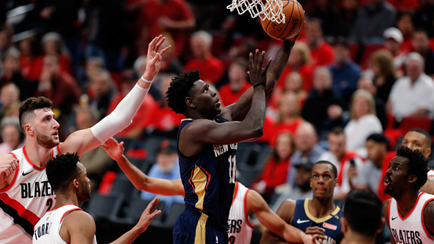 Jrue Holiday #11 of the New Orleans Pelicans drives against Ed Turner #1 and Jusuf Nurkic #27 of the Portland Trail Blazers during Game One of the Western Conference Quarterfinals during the 2018 NBA Playoffs at Moda Center on April 17, 2018 in Portland, Oregon.