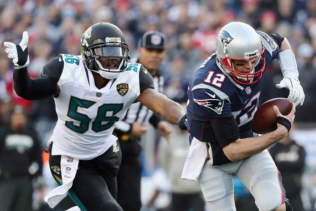 Tom Brady #12 of the New England Patriots is pursued by Dante Fowler Jr. #56 of the Jacksonville Jaguars in the first quarter during the AFC Championship Game at Gillette Stadium on January 21, 2018 in Foxborough, Massachusetts.