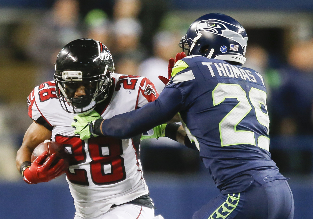 Running back Terron Ward #28 of the Atlanta Falcons tries to stiff-arm free safety Earl Thomas #29 of the Seattle Seahawks during the fourth quarter of the game at CenturyLink Field on November 20, 2017 in Seattle, Washington.