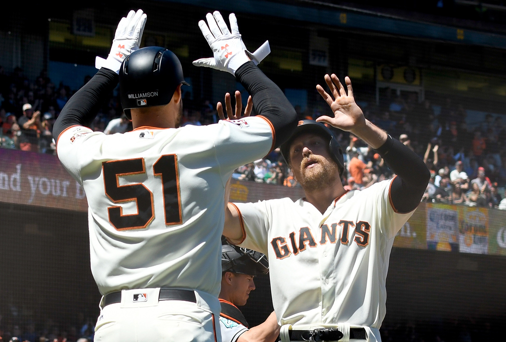 Mac Williamson #51 and Hunter Pence #8 of the San Francisco Giants celebrates after they both score against the Miami Marlins in the bottom of the six inning at AT&T Park on June 20, 2018 in San Francisco, California. Williamson and Pence scored on a two-run rbi single from Gorkys Hernandez #7.