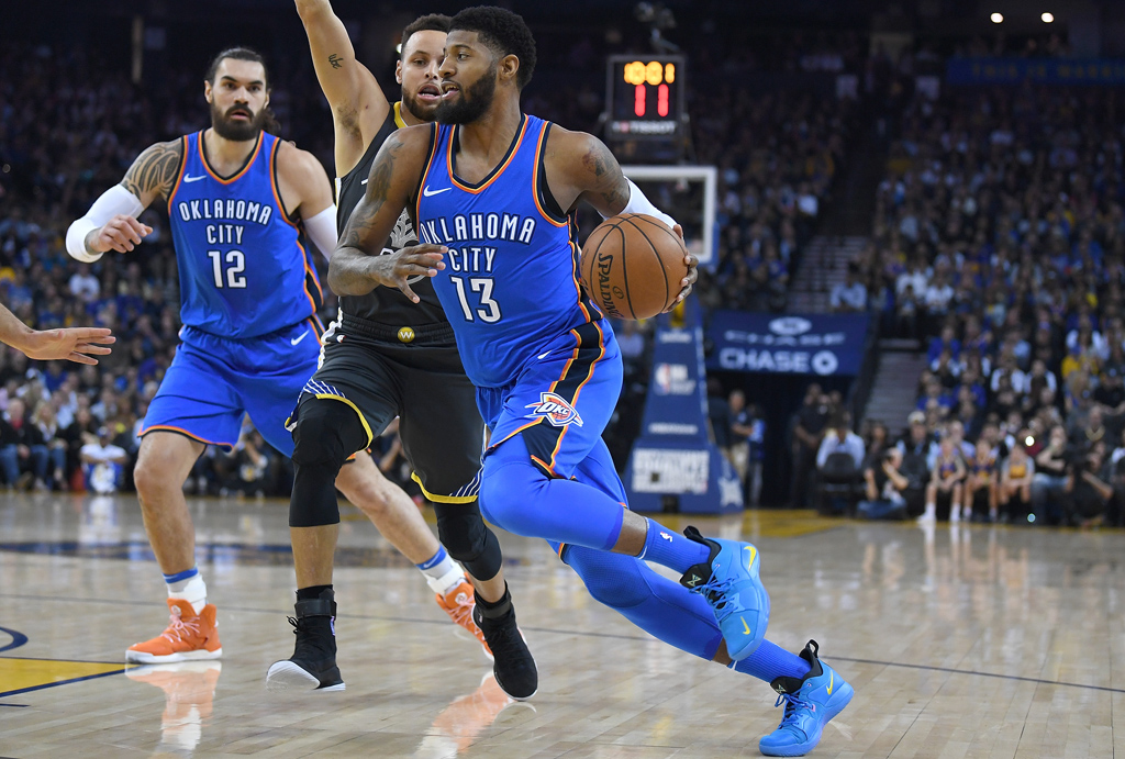 Paul George #13 of the Oklahoma City Thunder dribbles the ball towards the basket while guarded by Stephen Curry #30 of the Golden State Warriors during their NBA basketball game at ORACLE Arena on February 6, 2018 in Oakland, California.