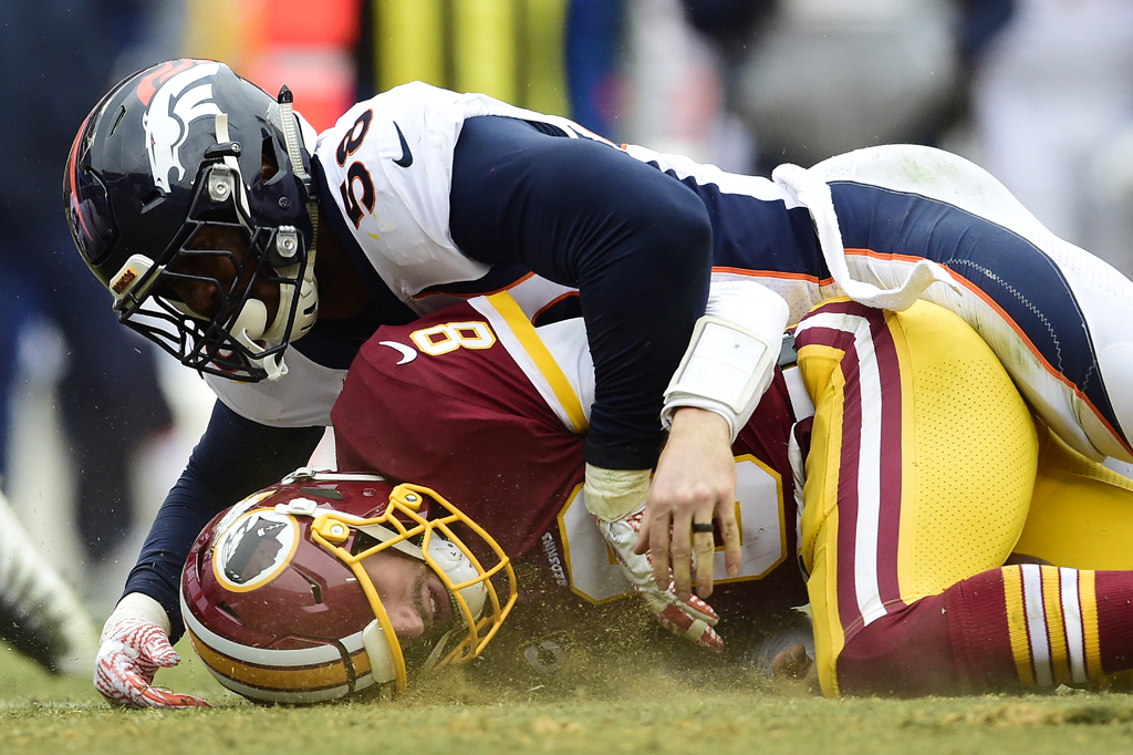 Quarterback Kirk Cousins #8 of the Washington Redskins is sacked by outside linebacker Von Miller #58 of the Denver Broncos in the second quarter at FedExField on December 24, 2017 in Landover, Maryland.