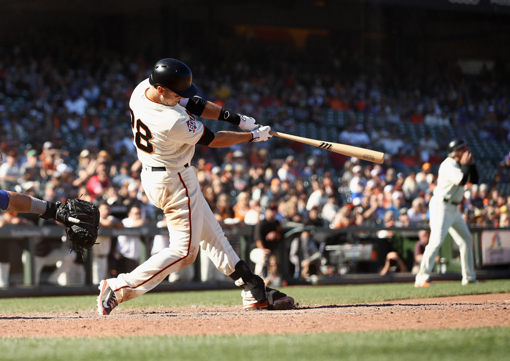 Buster Posey #28 of the San Francisco Giants hits the game winning hit in the bottom of the 13th inning to beat the Chicago Cubs at AT&T Park on July 11, 2018 in San Francisco, California.