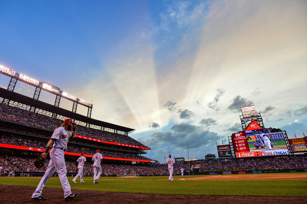 Charlie Blackmon #19 of the Colorado Rockies and his teammates take the field for the eighth inning as stripes from the setting sun appear in the sky at Coors Field on July 4, 2018 in Denver, Colorado.