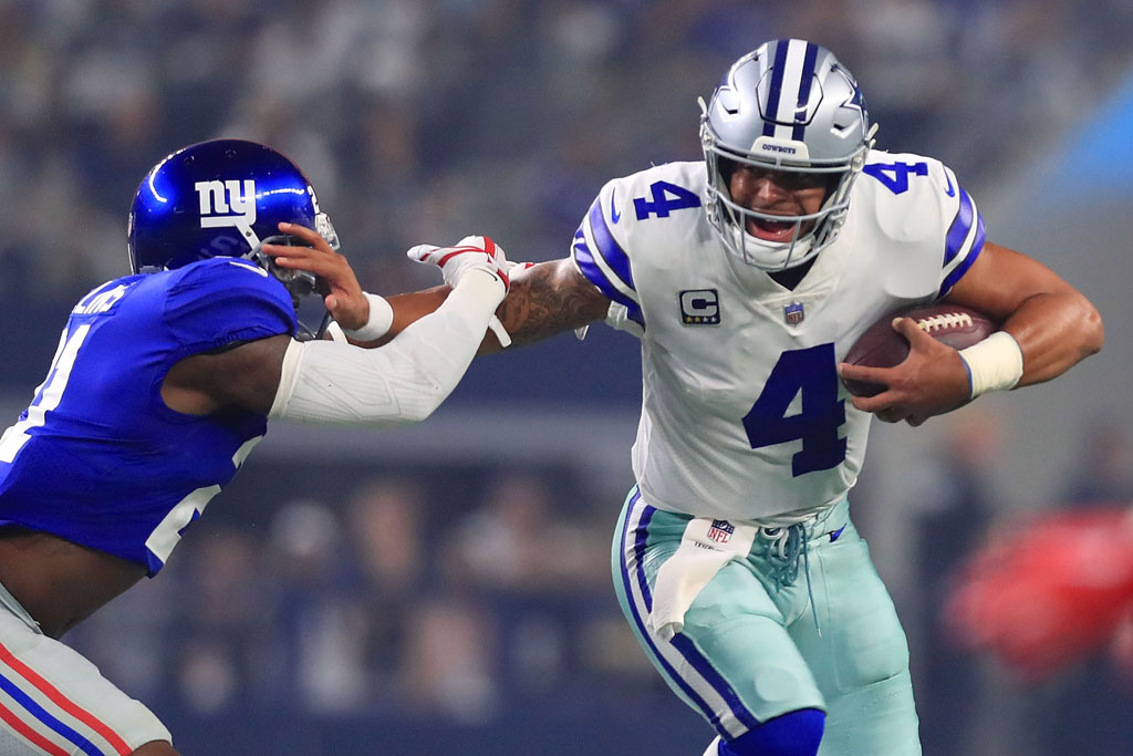 Landon Collins #21 of the New York Giants tries to grab Dak Prescott #4 of the Dallas Cowboys in the first quarter of a football game at AT&T Stadium on September 16, 2018 in Arlington, Texas.