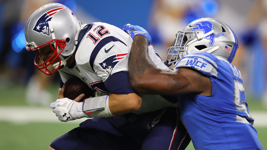 Tom Brady #12 of the New England Patriots is sacked in the fourth quarter by Eli Harold #57 of the Detroit Lions at Ford Field on September 23, 2018 in Detroit, Michigan.