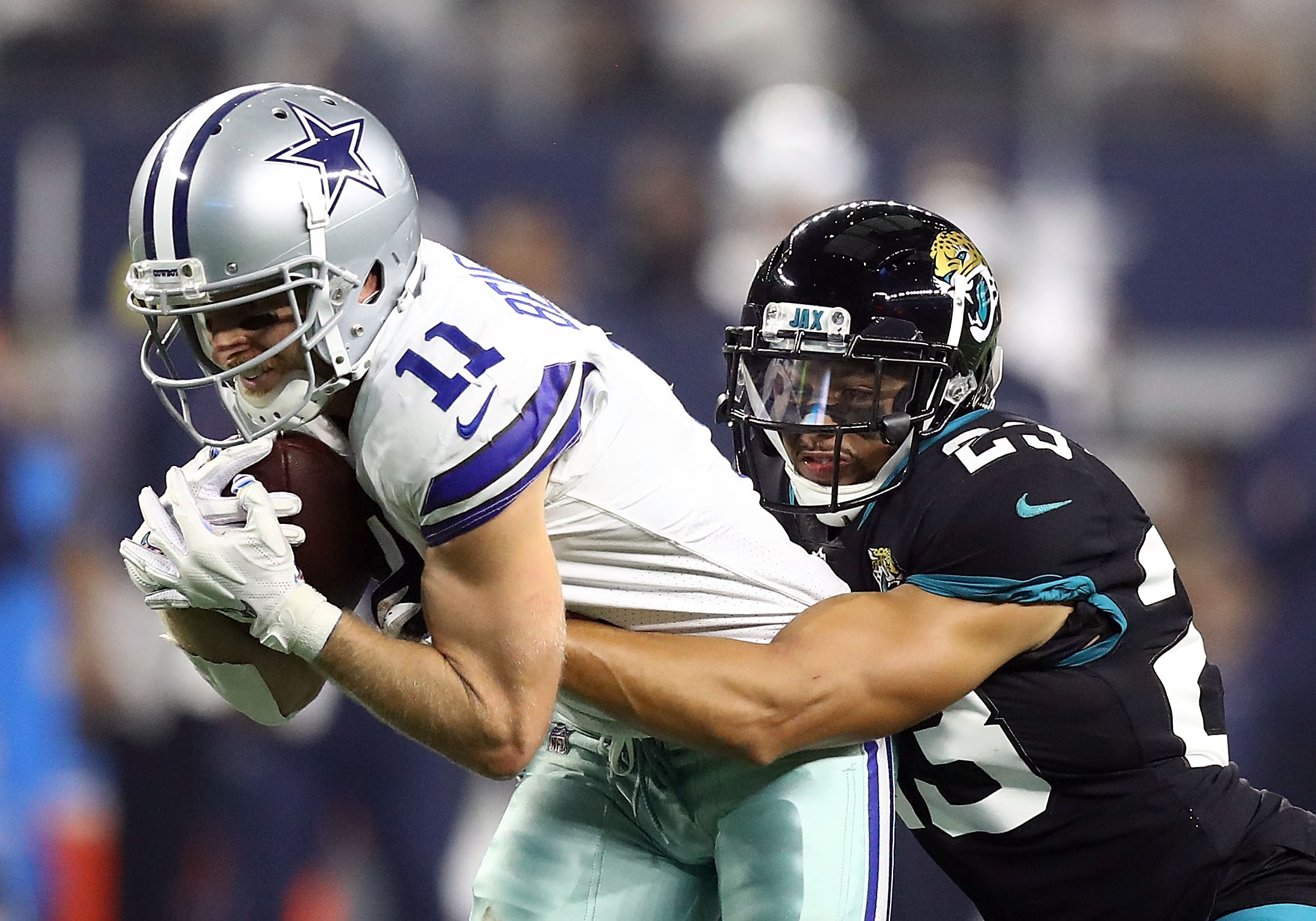 Cole Beasley #11 of the Dallas Cowboys gets tackled by Tyler Patmon #23 of the Jacksonville Jaguars in the second quarter of a game at AT&T Stadium on October 14, 2018 in Arlington, Texas.