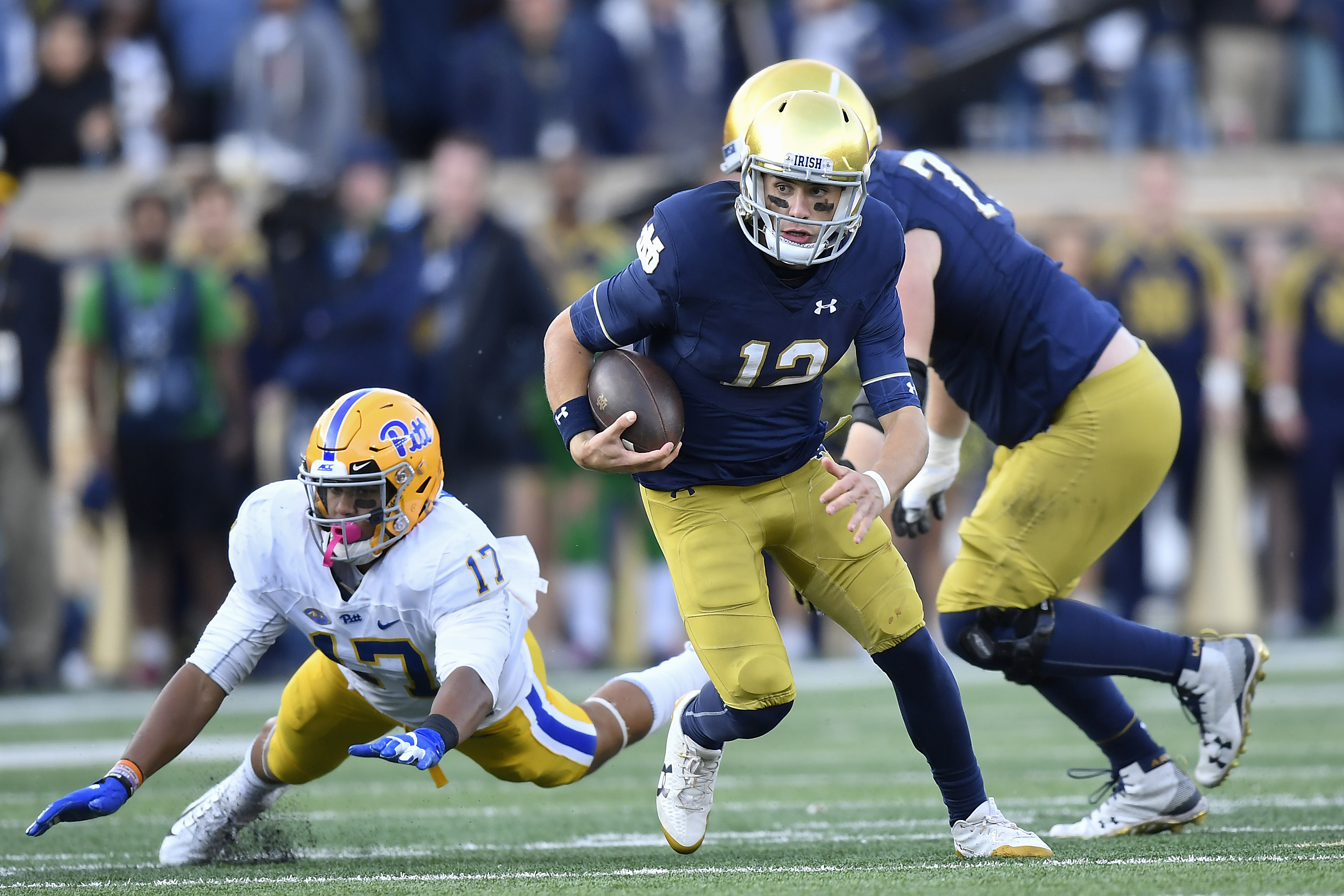 Ian Book #12 of the Notre Dame Fighting Irish scramble to avoid the tackle from Rashad Weaver #17 of the Pittsburgh Panthers in the second half at Notre Dame Stadium on October 13, 2018 in South Bend, Indiana.
