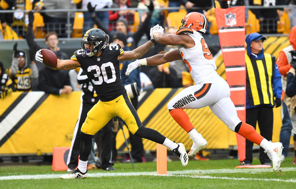 James Conner #30 of the Pittsburgh Steelers stretches past Myles Garrett #95 of the Cleveland Browns for a 12 yard touchdown during the third quarter in the game at Heinz Field on October 28, 2018 in Pittsburgh, Pennsylvania.