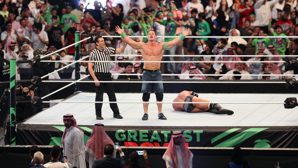 John Cena (C) celebrates defeating Triple H (R) during the World Wrestling Entertainment (WWE) Greatest Royal Rumble event in the Saudi coastal city of Jeddah on April 27, 2018.