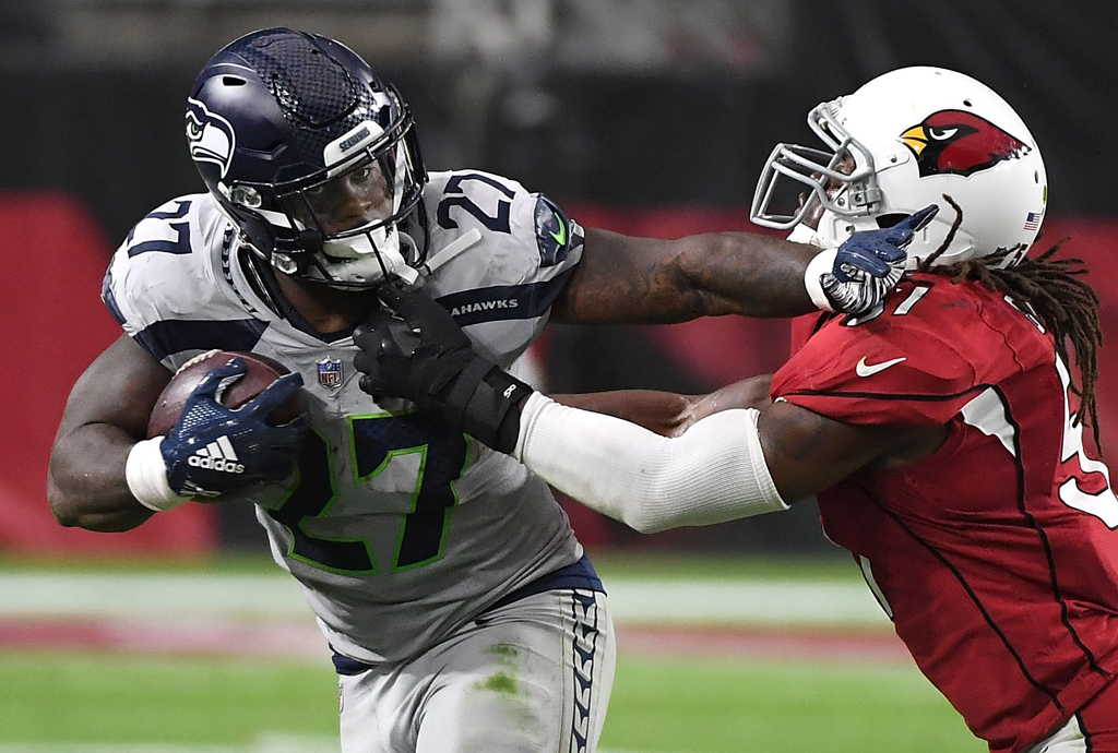 Running back Mike Davis #27 of the Seattle Seahawks stiff arms linebacker Josh Bynes #57 of the Arizona Cardinals during the second quarter at State Farm Stadium on September 30, 2018 in Glendale, Arizona.