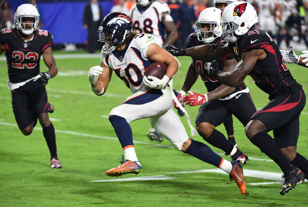 Running back Phillip Lindsay #30 of the Denver Broncos runs past cornerback Patrick Peterson #21 and linebacker Haason Reddick #43 of the Arizona Cardinals for a touchdown during the third quarter at State Farm Stadium on October 18, 2018 in Glendale, Arizona.