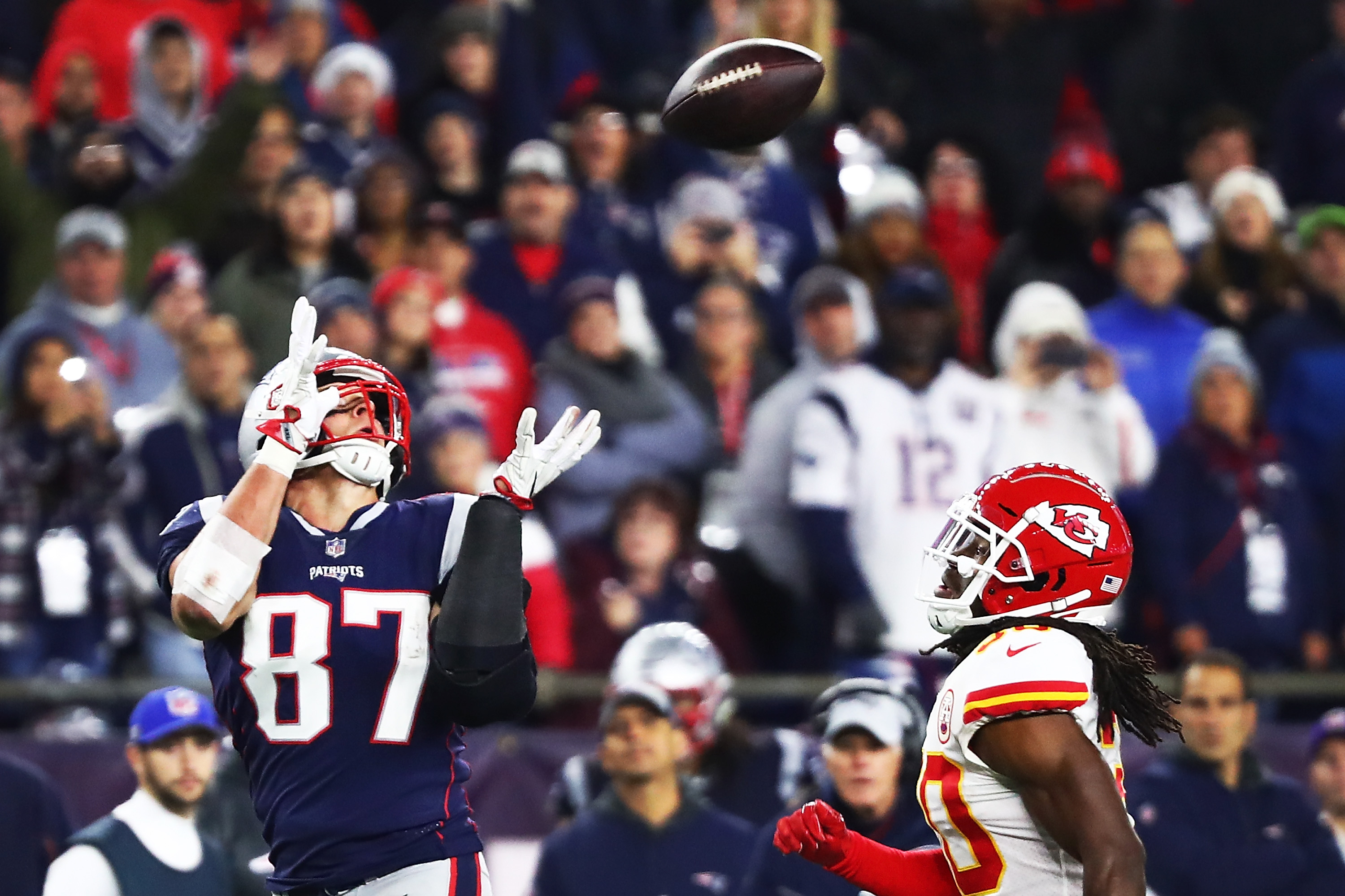 Rob Gronkowski #87 of the New England Patriots makes a catch while under pressure from Josh Shaw #30 of the Kansas City Chiefs in the fourth quarter of a game at Gillette Stadium on October 14, 2018 in Foxborough, Massachusetts.