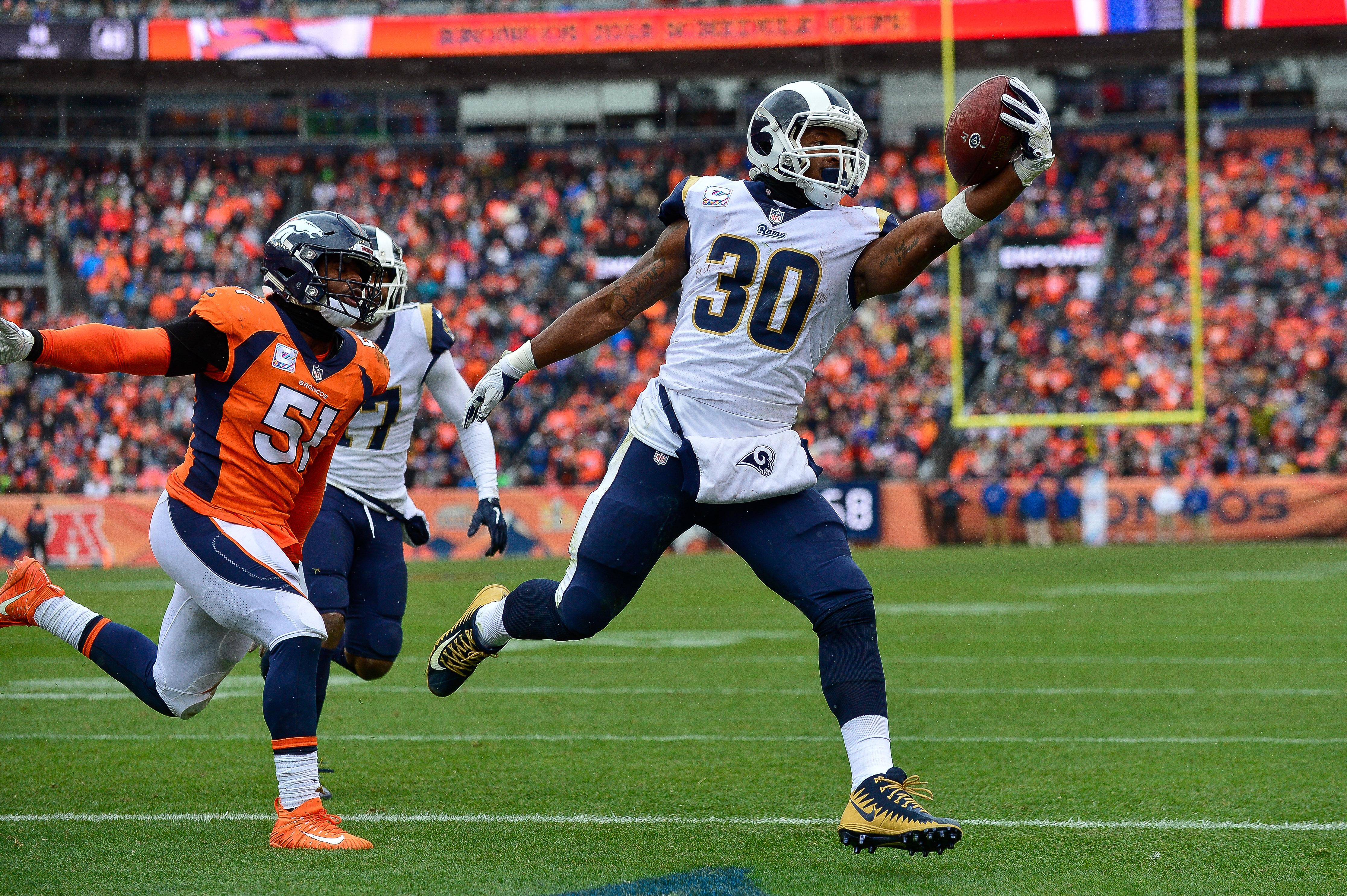 Running back Todd Gurley #30 of the Los Angeles Rams scores a second quarter rushing touchdown as linebacker Todd Davis #51 of the Denver Broncos attempts to tackle him during a game at Broncos Stadium at Mile High on October 14, 2018 in Denver, Colorado.