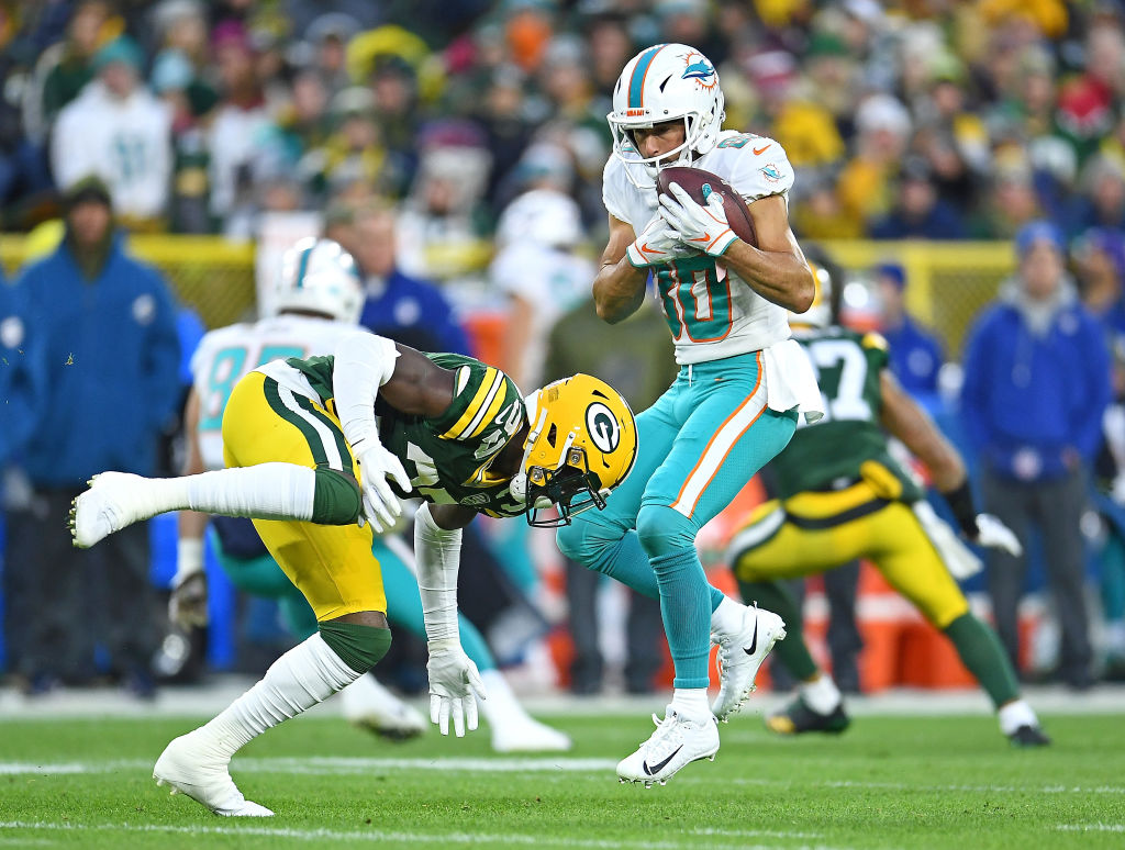 Danny Amendola #80 of the Miami Dolphins makes a catch in front of Josh Jackson #37 of the Green Bay Packers during the first half of a game at Lambeau Field on November 11, 2018 in Green Bay, Wisconsin.