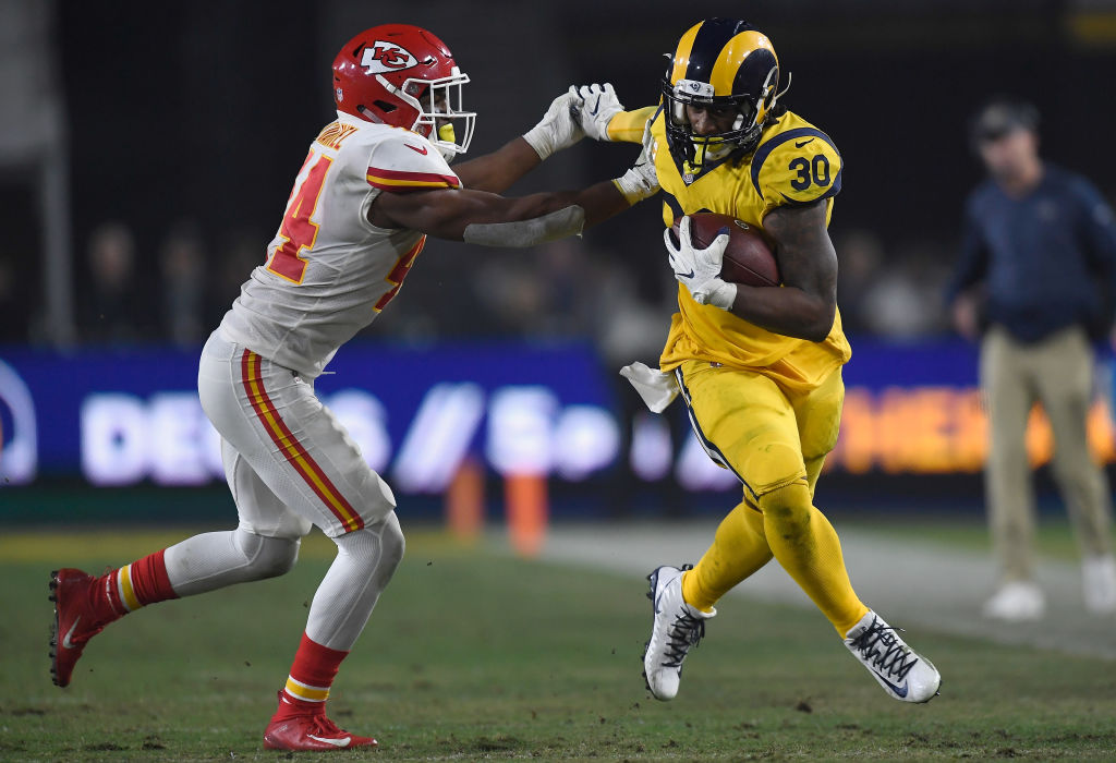 Todd Gurley #30 of the Los Angeles Rams fends off Dorian O'Daniel #44 of the Kansas City Chiefs during the third quarter of the game at Los Angeles Memorial Coliseum on November 19, 2018 in Los Angeles, California.