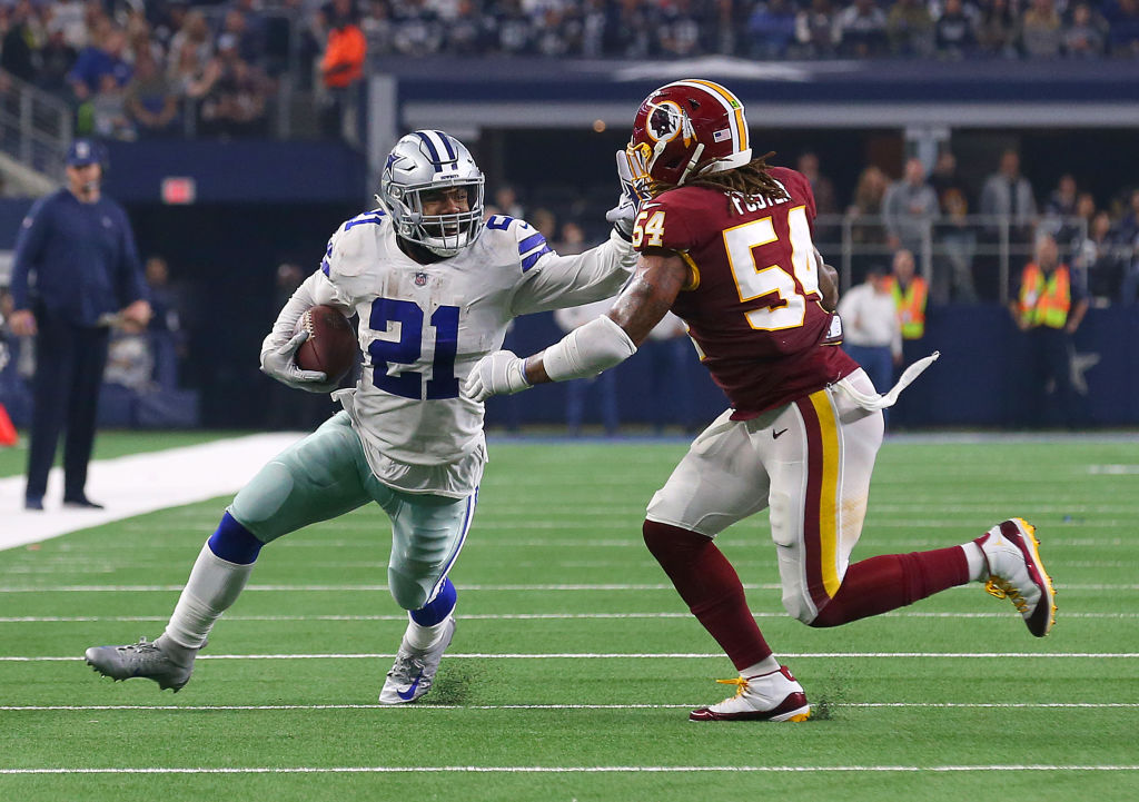 Ezekiel Elliott #21 of the Dallas Cowboys holds off Mason Foster #54 of the Washington Redskins on a run in the fourth quarter at AT&T Stadium on November 22, 2018 in Arlington, Texas.