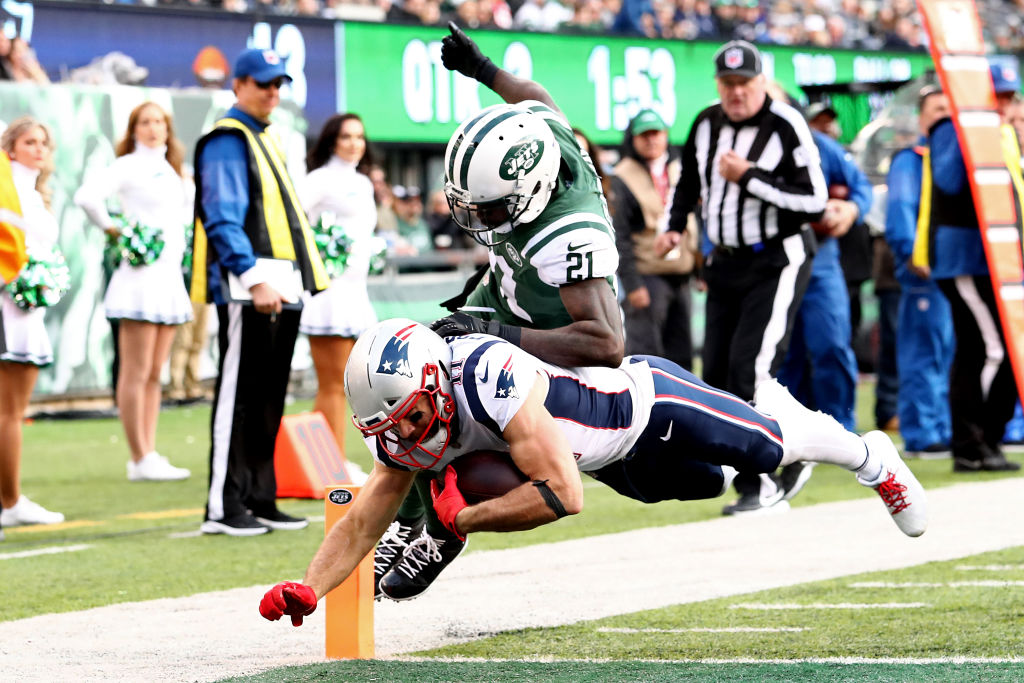 Julian Edelman #11 of the New England Patriots dives into the end zone for a third quarter touchdown past Morris Claiborne #21 of the New York Jets at MetLife Stadium on November 25, 2018 in East Rutherford, New Jersey.