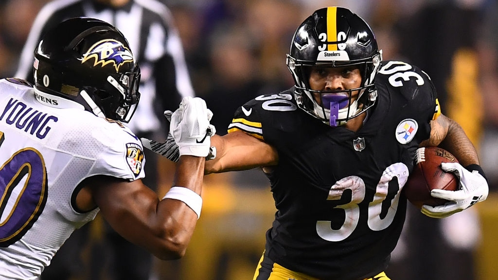 James Conner #30 of the Pittsburgh Steelers stiff arms Kenny Young #40 of the Baltimore Ravens as he carries the ball in the first half during the game at Heinz Field on September 30, 2018 in Pittsburgh, Pennsylvania.