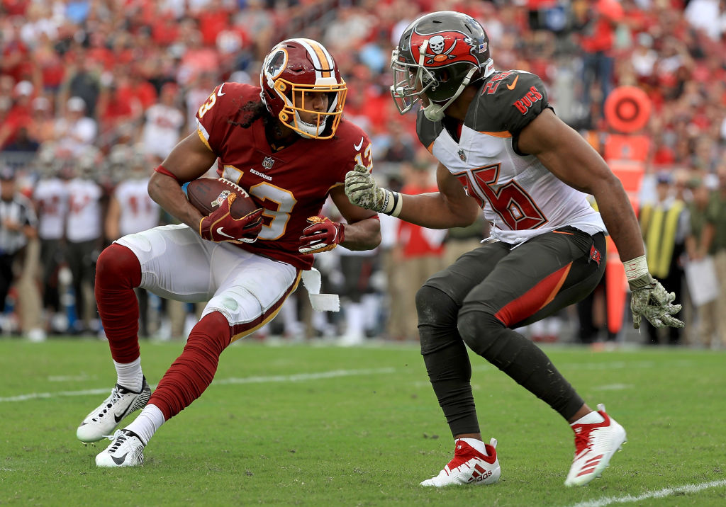 Maurice Harris #13 of the Washington Redskins is defended by Andrew Adams #26 of the Tampa Bay Buccaneers during a game at Raymond James Stadium on November 11, 2018 in Tampa, Florida.