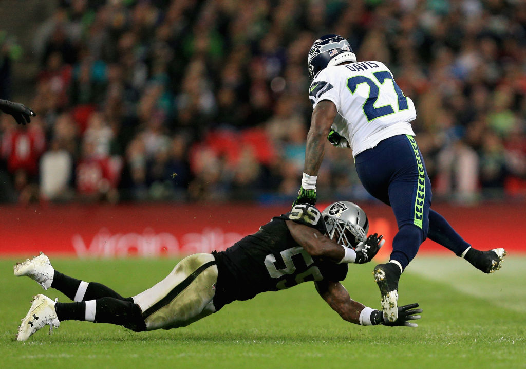 Mike Davis of Seattle Seahawks escapes the tackle of Marquel Lee of Oakland Raiders during the NFL International series match between Seattle Seahawks and Oakland Raiders at Wembley Stadium on October 14, 2018 in Lond