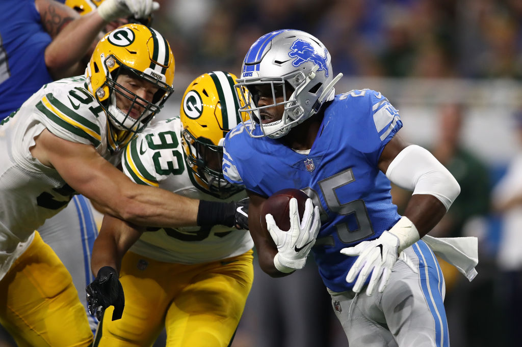Theo Riddick #25 of the Detroit Lions runs the ball against Kyler Fackrell #51 of the Green Bay Packers and Reggie Gilbert #93 during the second half at Ford Field on October 7, 2018 in Detroit, Michigan.