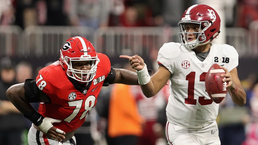 Quarterback Tua Tagovailoa #13 of the Alabama Crimson Tide scrambles with the football ahead of defensive tackle Trenton Thompson #78 of the Georgia Bulldogs during the CFP National Championship presented by AT&T at Mercedes-Benz Stadium on January 8, 2018 in Atlanta, Georgia. The Crimson Tide defeated the Bulldogs 26-23.