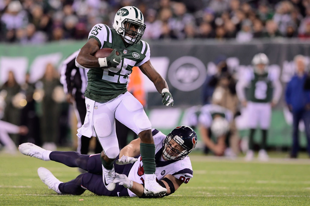 Running back Elijah McGuire #25 of the New York Jets runs the ball against defensive end J.J. Watt #99 of the Houston Texans during the third quarter at MetLife Stadium on December 15, 2018 in East Rutherford, New Jersey.
