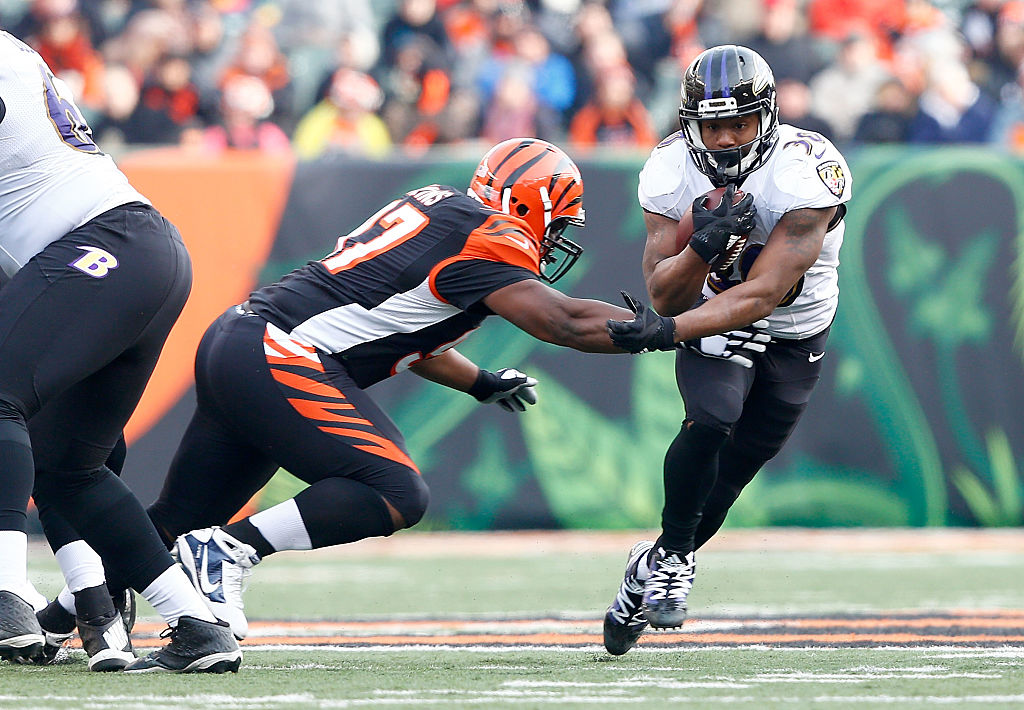 Kenneth Dixon #30 of the Baltimore Ravens breaks an attempted tackle by Geno Atkins #97 of the Cincinnati Bengals during the third quarter at Paul Brown Stadium on January 1, 2017 in Cincinnati, Ohio.