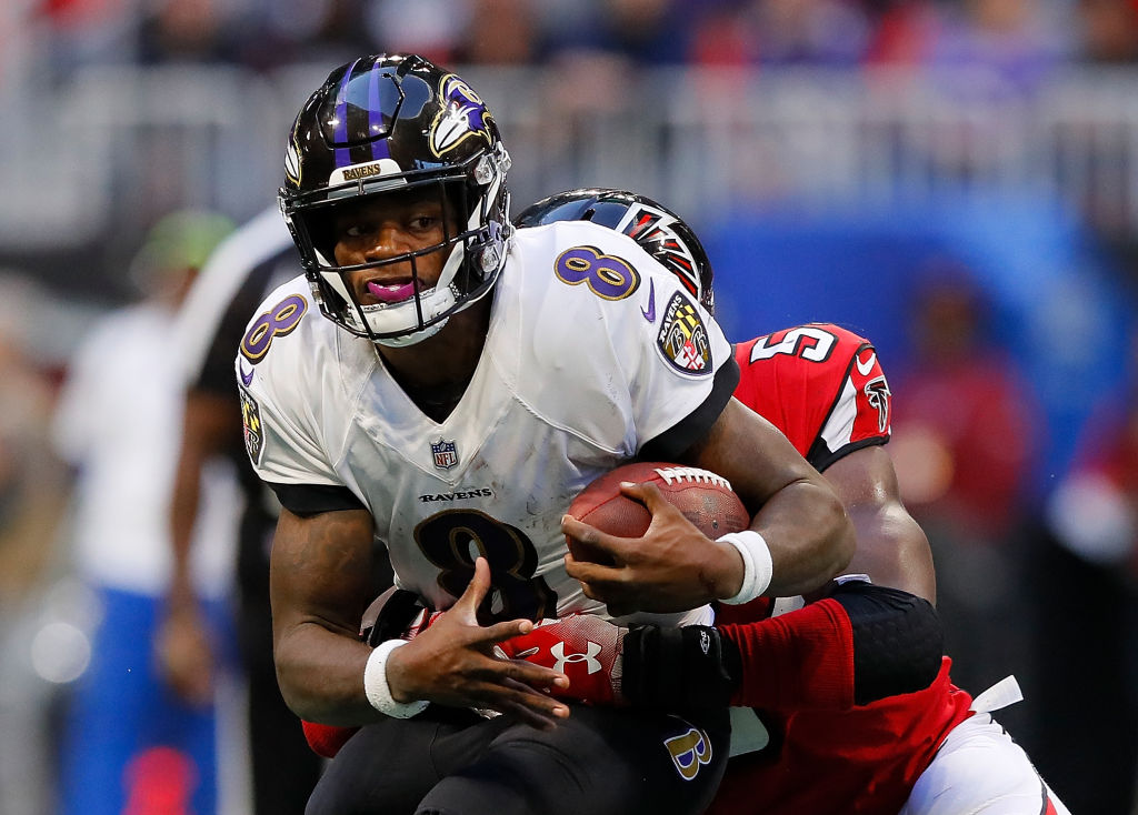Lamar Jackson #8 of the Baltimore Ravens rushes against Foye Oluokun #54 of the Atlanta Falcons at Mercedes-Benz Stadium on December 2, 2018 in Atlanta, Georgia.