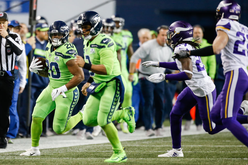 Rashaad Penny #20 of the Seattle Seahawks runs the ball with Russell Wilson #3 as the lead blocker in the second quarter against the Minnesota Vikings at CenturyLink Field on December 10, 2018 in Seattle, Washington.