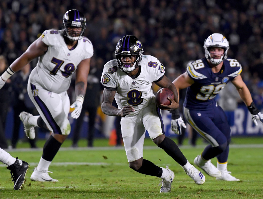Lamar Jackson #8 of the Baltimore Ravens scrambles short of a first down in front of Joey Bosa #99 of the Los Angeles Chargers and Orlando Brown #78 during the second quarter at StubHub Center on December 22, 2018 in Carson, California.