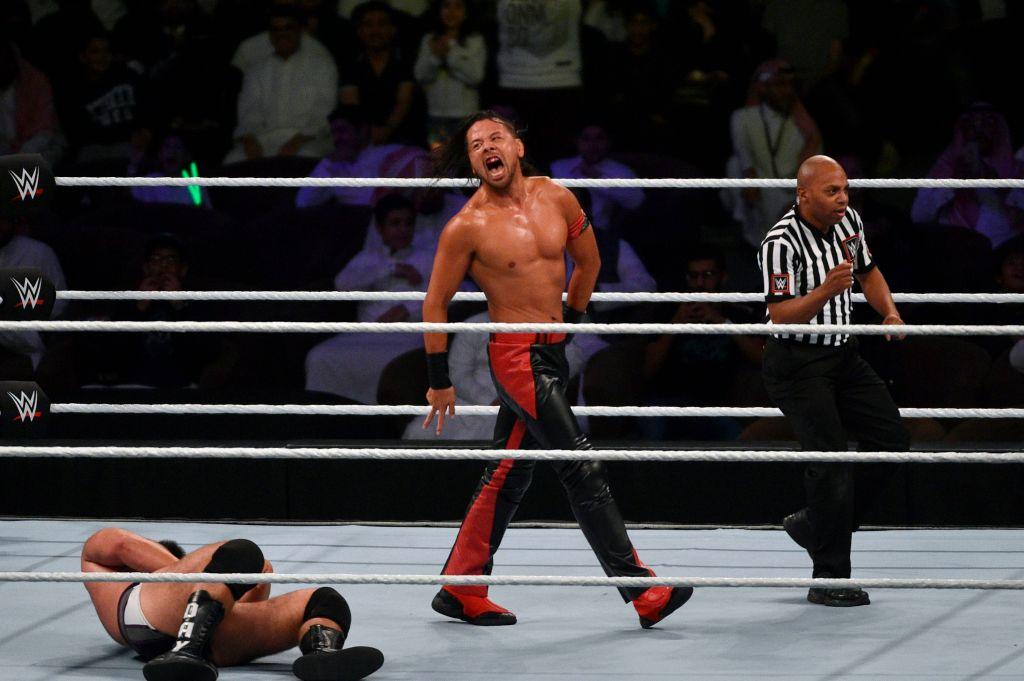 Shinsuke Nakamura (C) celebrates after defeating Rusev (L) for the for the WWE United States Championship during the World Wrestling Entertainment (WWE) Crown Jewel pay-per-view at the King Saud University Stadium in Riyadh on November 2, 2018.