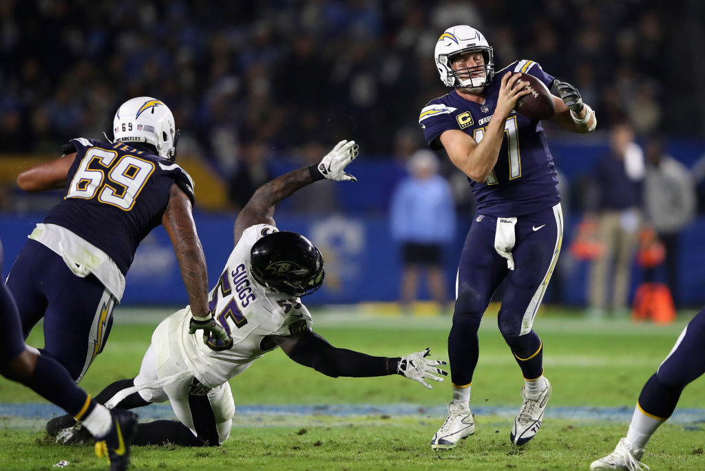 Sam Tevi #69 blocks as Philip Rivers #17 of the Los Angeles Chargers eludes a tackle by Terrell Suggs #55 of the Baltimore Ravens during the second half of a game at StubHub Center on December 22, 2018 in Carson, California.