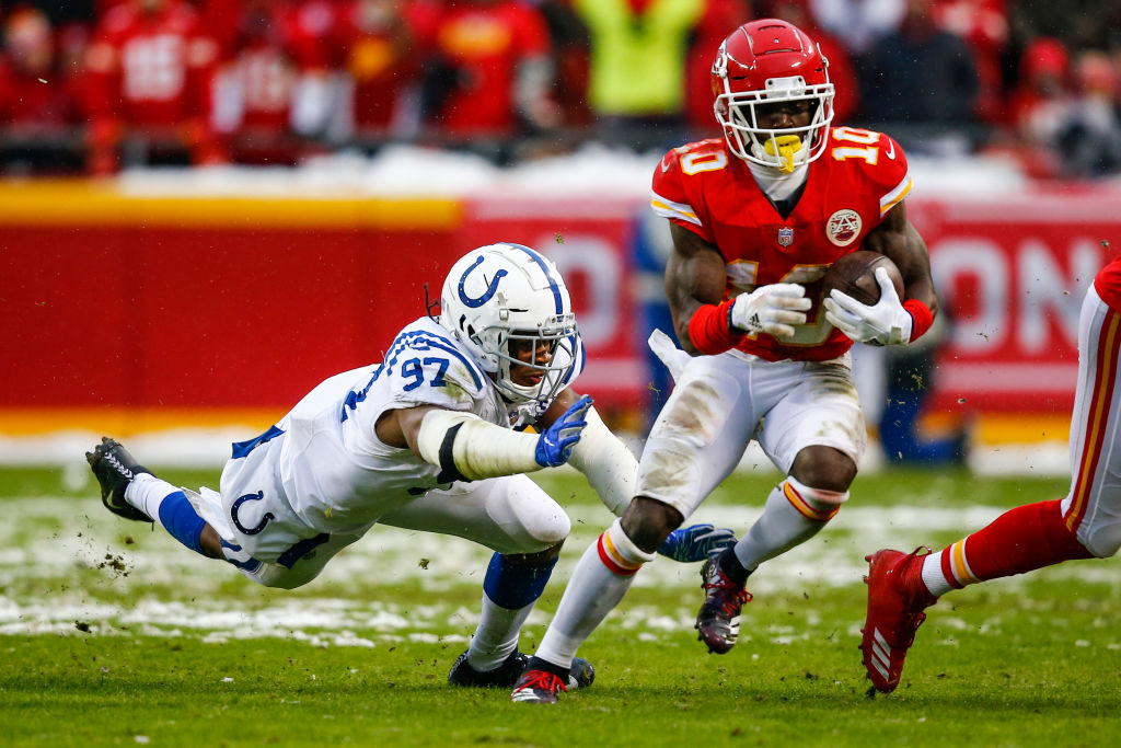 Tyreek Hill #10 of the Kansas City Chiefs tries to avoid the diving tackle attempt of Al-Quadin Muhammad #97 of the Indianapolis Colts during the first quarter of the AFC Divisional Round playoff game at Arrowhead Stadium on January 12, 2019 in Kansas City, Missouri.