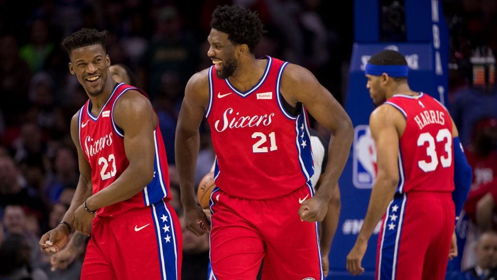 Jimmy Butler #23 and Joel Embiid #21 of the Philadelphia 76ers share a laugh as Tobias Harris #33 looks on in the fourth quarter against the Denver Nuggets at the Wells Fargo Center on February 8, 2019 in Philadelphia, Pennsylvania. The 76ers defeated the Nuggets 117-110.